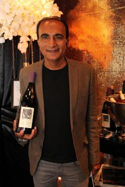 "Iqbal Theba of ""Glee"" with a Merry Edwards magnum in the gift lounge at the Academy Awards, March 2012"